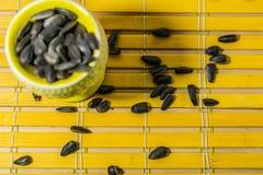 Zwarte kleine zonnebloemzaden Klik zaden met schillen Een handvol in een gele miniatuurtribune op een houten servet Morste sommig stock foto's