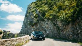 Zwarte kleur Seat Leon 5 deurauto op achtergrond van Franse berg Stock Fotografie