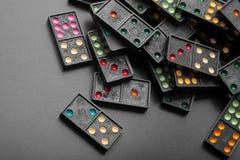 Zwarte kleurendomino's die op donkere achtergrond liggen Royalty-vrije Stock Foto's