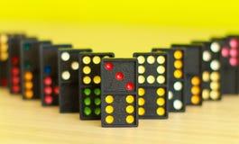 Zwarte kleurendomino's met kleurrijke punt op lijst Stock Afbeeldingen