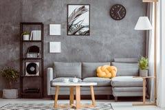 Zwarte klok boven grijze sofa royalty-vrije stock afbeeldingen
