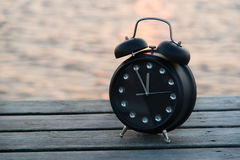 Zwarte klok 5 minuten in 12 op een pier bij zonsondergang Royalty-vrije Stock Foto