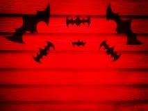Zwarte knuppels op rode muur Stock Foto's