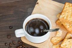 Zwarte koffie, cracker en koffieboon op hout met warme ochtend stock afbeeldingen