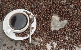 Zwarte koffie die door bonen met hart gestalte gegeven gat, koffie wordt omringd royalty-vrije stock afbeeldingen