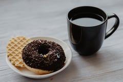 Zwarte koffie in een zwarte mok en doughnut met wafeltje op een plaat stock afbeelding