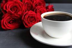 Zwarte koffie in een witte Kop met een schotel op de lijst, een boeket van rode rozen royalty-vrije stock afbeeldingen