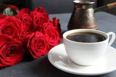 Zwarte koffie in een witte Kop met een schotel op de lijst, een boeket van rode rozen stock foto's