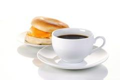 Zwarte koffie en een ongezuurd broodje stock afbeeldingen