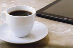 Zwarte koffie en een tablet Stock Foto