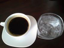 Zwarte koffie en wat water stock foto