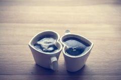 Zwarte koffie, espresso in twee hart gevormde koppen Liefde, de Dag van Valentine, wijnoogst Stock Foto