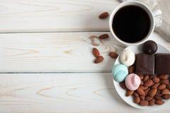 Zwarte koffie met snoepjes en amandelen op houten achtergrond De ruimte van het exemplaar Hoogste mening Royalty-vrije Stock Fotografie