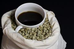 Zwarte koffie op bonen. Stock Foto