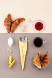 Zwarte koffie, room, croissants, jam en vers fruit op een licht Stock Fotografie