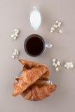 Zwarte koffie, room, verse croissants en toost op een licht beige Royalty-vrije Stock Afbeelding
