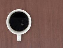 Zwarte koffie in witte ceramische koffiekop op donkere bruine houten lijstvloer stock foto