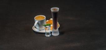Zwarte koffie in witte kop, met croissants op schotel, likeur royalty-vrije stock afbeeldingen