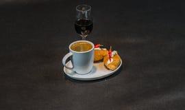 Zwarte koffie in witte kop, met croissants op schotel, likeur, p stock foto