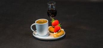 Zwarte koffie in witte kop, met croissants op schotel, likeur, s stock afbeelding