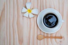 Zwarte koffie in witte kop met witte plumeriabloem op houten B Stock Foto