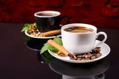 Zwarte Koffie in Zwart-witte Koppen met Kruiden Stock Fotografie