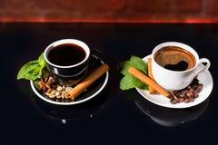 Zwarte Koffie in Zwart-witte Koppen met Kruiden Stock Foto