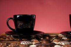 Zwarte koffiekop over chocoladesnoepjes. Stock Foto