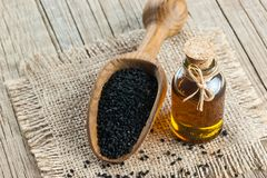 Zwarte komijnzaden en etherische olie met kom en houten schop of lepel stock afbeeldingen