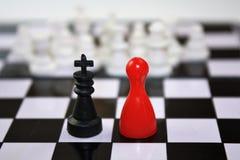 Zwarte koning en het rode beeldje van de damekoningin van Ludo en witte onscherpe schaakstukken in de afstand Op het interessante Royalty-vrije Stock Afbeelding
