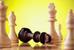 Zwarte koning neer gevallen, omringd door witte stukken Royalty-vrije Stock Foto
