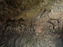 Zwarte koolstofpaarden op zandsteenmuur Verf van de jacht, voorhistorisch beeld Royalty-vrije Stock Afbeelding