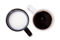 Zwarte kop met melk en een witte kop met zwarte koffie. Stock Fotografie