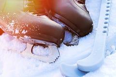 Zwarte kunstschaatsen die in de sneeuw en de heldere zon liggen Stock Fotografie