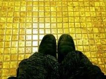 Zwarte laarzen op gouden tegels Stock Foto's