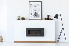 Zwarte lamp naast open haard en affiche in het witte minimale leven royalty-vrije stock foto's