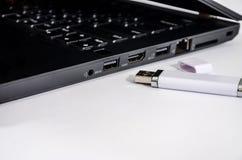 Zwarte laptop en flitsaandrijving op een witte achtergrond stock afbeelding