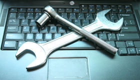 Zwarte laptop met een moersleutel op het toetsenbord Royalty-vrije Stock Afbeeldingen