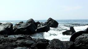 Zwarte lavarotsen met oceaangolven Kona Hawaï stock video
