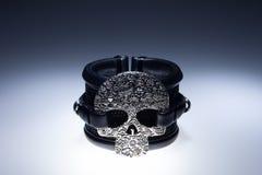 Zwarte leerarmband met de tegenhanger van de metaalschedel en zwarte stenen Stock Afbeelding