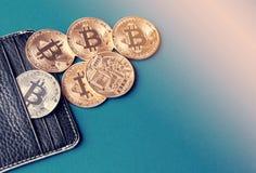 Zwarte leerportefeuille op een blauwe achtergrond met verscheidene gouden en zilveren muntstukken van bitcoins die van hun zakken Stock Foto's