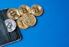 Zwarte leerportefeuille op een blauwe achtergrond met verscheidene gouden en zilveren muntstukken van bitcoins die van hun zakken Stock Foto