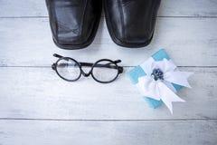 Zwarte leerschoenen en zwarte oogglazen met blauwe giftdoos Royalty-vrije Stock Afbeeldingen