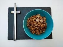 Zwarte leibasis met blauwe kom van kekers met tofu en ui met metaaleetstokjes op witte achtergrond stock fotografie
