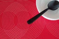 Zwarte lepel in een witte kom op een rood tafelkleed stock foto