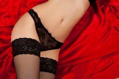 Zwarte lingerie op rode zijde Stock Fotografie