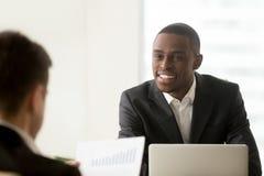 Zwarte manager die met witte cliënt communiceren stock afbeelding