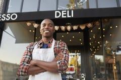 Zwarte mannelijke bedrijfseigenaar die zich buiten koffiewinkel bevinden stock fotografie