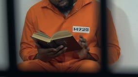 Zwarte mannelijke gevangene die heilige bijbel in cel, hoop voor vergiffenis, penitentie lezen stock footage