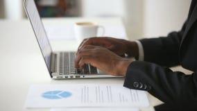 Zwarte mannelijke handen die op laptop toetsenbord bij bureau typen stock footage